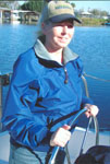 Here is a West Marine Jacket Contest winner in her blue jacket st the wheel of her boat.